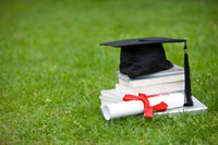 A stack of books and a diploma on the lawn