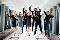 Business people jumping with hands outstretched and smiling