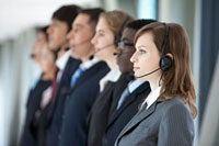 Business people standing in a row with headsets
