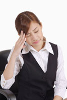 Young office lady sitting and having headache