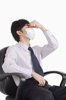Man sitting on chair and wearing surgical mask for headache