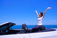Young woman sitting in the car with arms outstretched and lo