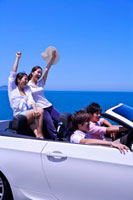 Four people driving in the car and enjoying leisure activity