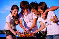 Four people barbecuing outside and smiling happily,