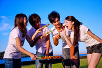 Four people barbecuing outside and eating food,