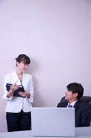 Man and woman talking in office and smiling at each other 11010043672| 写真素材・ストックフォト・画像・イラスト素材|アマナイメージズ