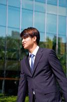 Young man walking and looking away 11010043714| 写真素材・ストックフォト・画像・イラスト素材|アマナイメージズ