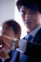 Young businessman looking down for the time 11010043717| 写真素材・ストックフォト・画像・イラスト素材|アマナイメージズ