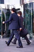 Two businessmen holding briefcase and walking away together