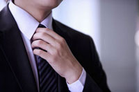 Young man holding tie with hand on chest 11010043783| 写真素材・ストックフォト・画像・イラスト素材|アマナイメージズ