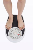 Young woman standing on weight scale