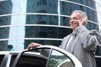 Senior businessman holding the door of car and using mobile 11010044177| 写真素材・ストックフォト・画像・イラスト素材|アマナイメージズ