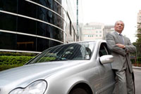 Senior businessman standing beside the car and looking up wi