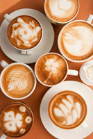Close-up of cups of cappuccino with different pattern on the