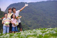 Young parents with two children holding vegetable and fruits