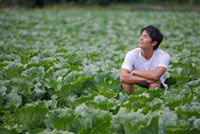 Young man sitting in the vegetable garden with eyes closed