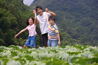 Young man with two children standing in the vegetable garden