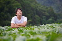 Young man closing eyes in the vegetable garden with smile