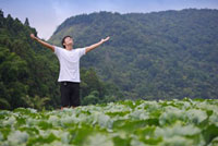 Young man standing in the vegetable garden and deep breathin
