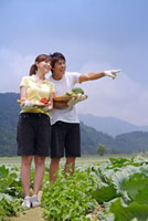 Young couple holding vegetables and smiling happily