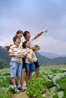 Young family with two children holding vegetables and lookin