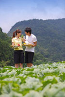 Young couple holding vegetables and eating with smile