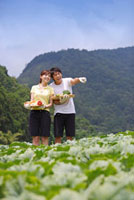 Young couple holding vegetables and looking away with smile