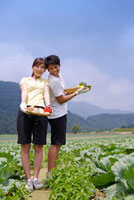 Young couple holding vegetables and smiling together