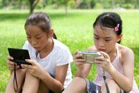 Two girls sitting together playing video games 11010044816  写真素材・ストックフォト・画像・イラスト素材 アマナイメージズ