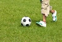 Boy playing football on lawn