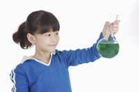 Girl holding laboratory glassware and looking away with smil