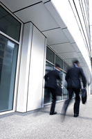 Businessmen rushing to work, rear view, blurred motion