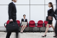 Business people walking in a hurry with a businesswoman sitt