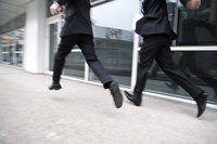 Businessmen running and leaping, blurred motion