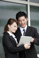 Businessman and businesswoman holding palmtop with smile