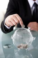 Businessman putting coins into piggy bank