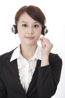 Businesswoman wearing headphone and looking at the camera wi