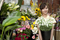 Female florist holding a pot of flowers in the flower shop