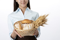 Female baker holding a basket of bread and wheat