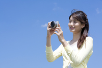 Young woman photographing and smiling