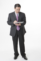 Business man holding note pad and looking down