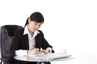 Businesswoman writing and looking down