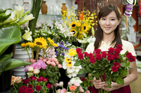 Female florist holding a bunch of rose in the flower shop