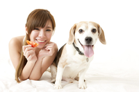 Young woman holding vegetable and bonding with a dog