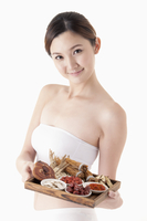 Young woman holding a tray with various kinds of Chinese her