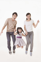 Young family jumping mid-air with smile together