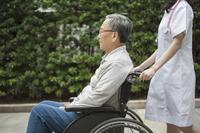 Nurse pushing wheel-chair for senior man