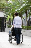 Senior woman pushing wheel-chair and walking