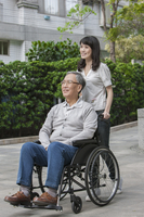 Young woman pushing wheel-chair for senior man