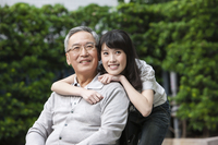 Young woman and senior man looking away with smile together